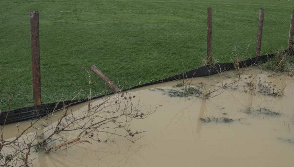 A failing silt fence holding back cubic meters of muddy water